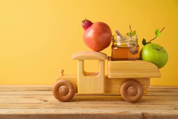 Jewish holiday Rosh Hashana concept with toy truck, honey, pomegranate and apples on wooden table over yellow background stock photo