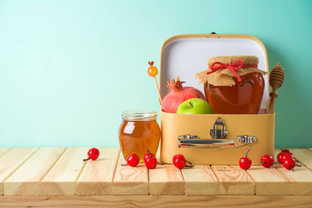 Jewish holiday Rosh Hashana creative gift background with suitecase box, honey jar, apple and pomegranate on wooden table. stock photo