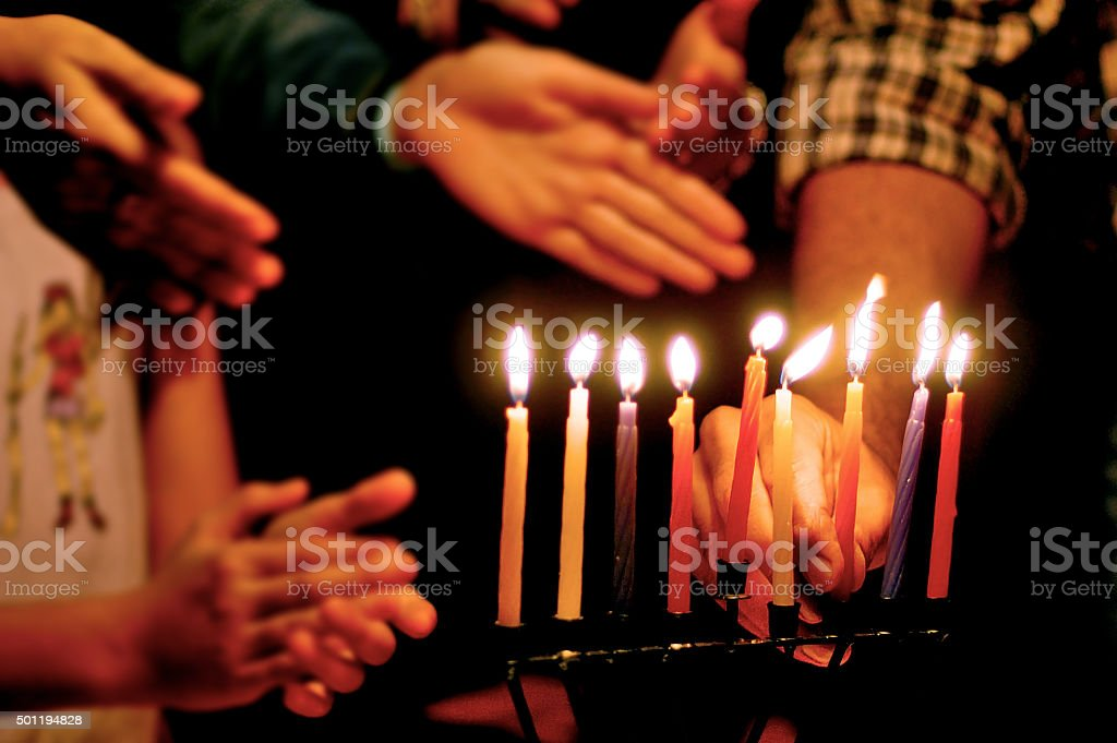 A family is lighting a candle for the Jewish holiday of Hanukkah that...