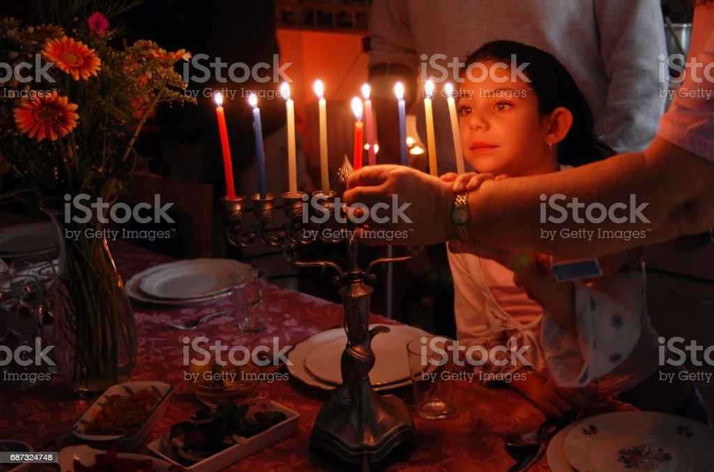A family is lighting a candle for the Jewish holiday of Hanukkah.