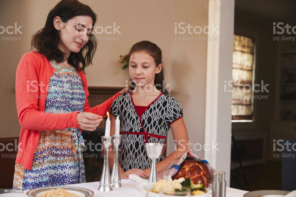 Jewish mother and daughter lighting candles for Shabbat meal stock photo