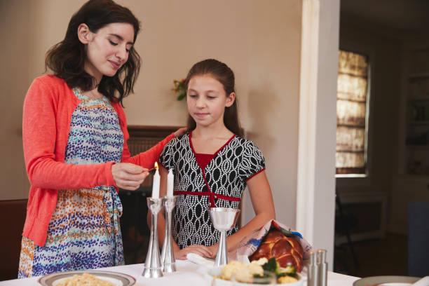madre judía e hija iluminación velas para comida de shabat - pascua judía fotografías e imágenes de stock