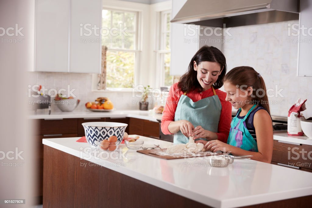 Jewish mother and daughter plaiting dough for challah bread stock photo