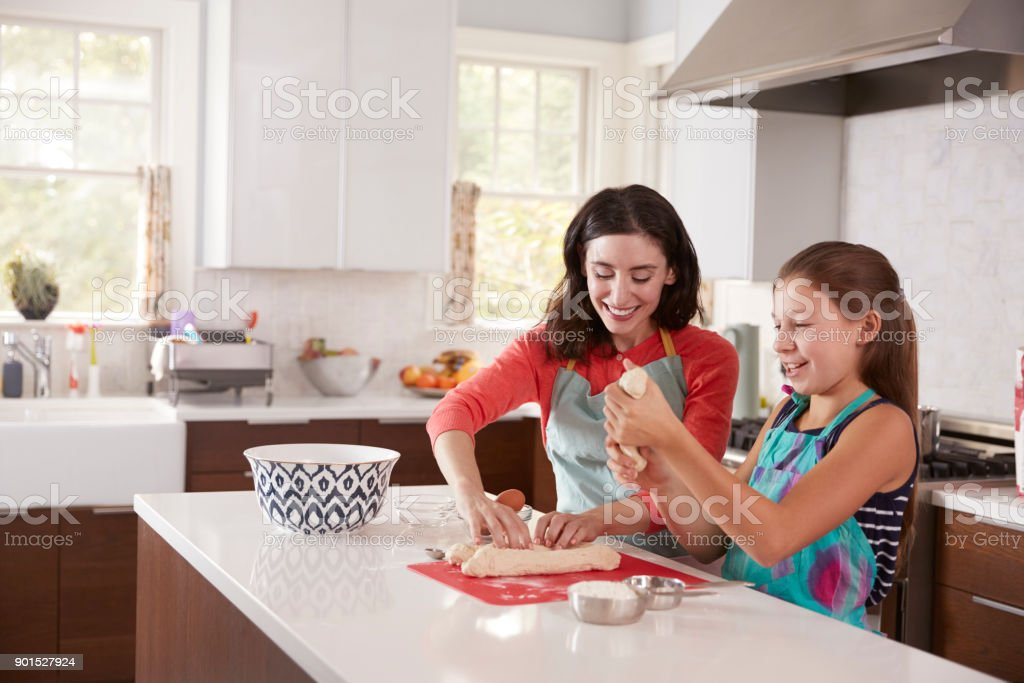 Jewish mother and daughter preparing dough for challah bread stock photo