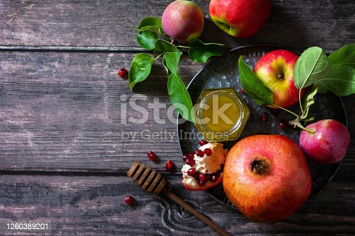 istock Jewish new year holiday concept. Traditional symbols: honey, fresh apples, pomegranate and shofar on a wooden table. Top view flat lay background. Copy space. 1260389201