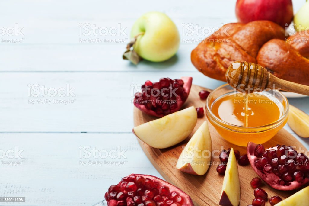 Jewish New Year Holiday, Rosh Hashana. Honey, apple slices, pomegranate and hala serve on wooden kitchen board. stock photo