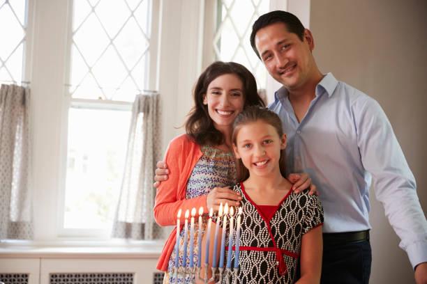 jüdische eltern und tochter lächelnd, brennende kerzen auf menora - freitag der 13 stock-fotos und bilder