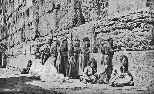 Jewish people at the Western Wall in Jerusalem, Israel. Vintage halftone photo etching circa late 19th century.