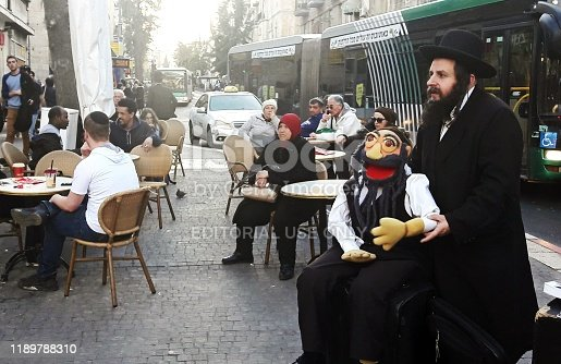 Man dressed in Orthodox Rabbi clothing works his marionette in front of a group of people in King George street in the center of Jerusalem.
