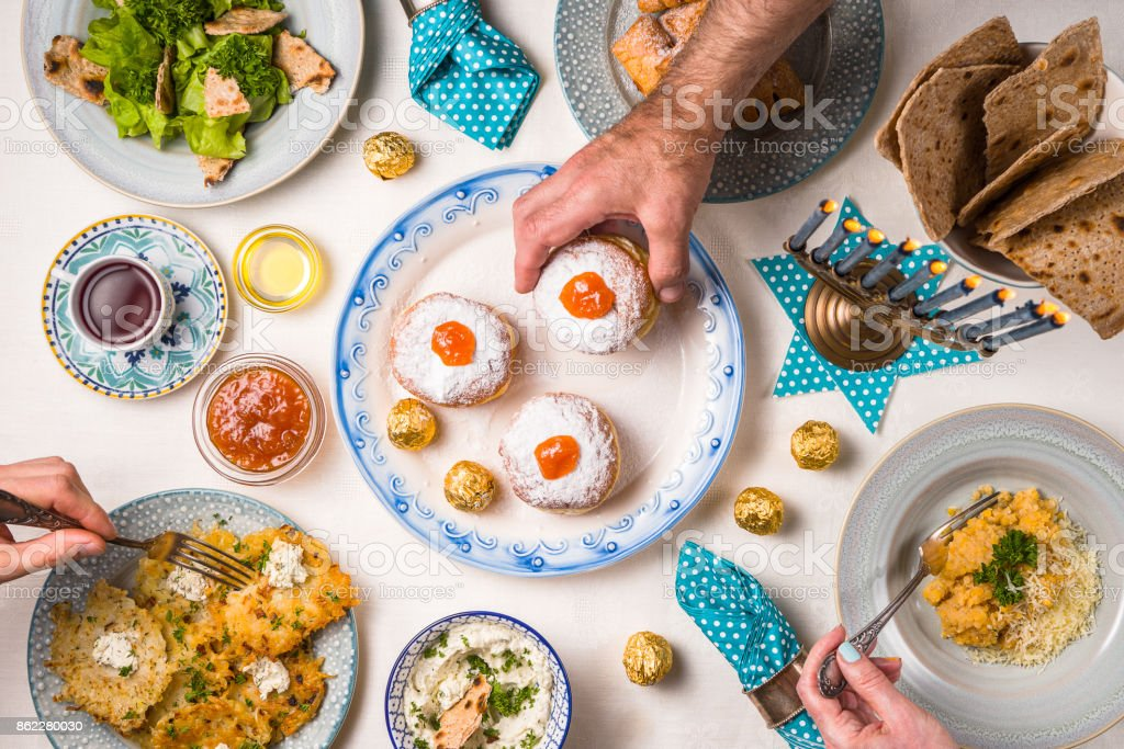 Jewish religious holiday Hanukkah, feast, hands over the table stock photo