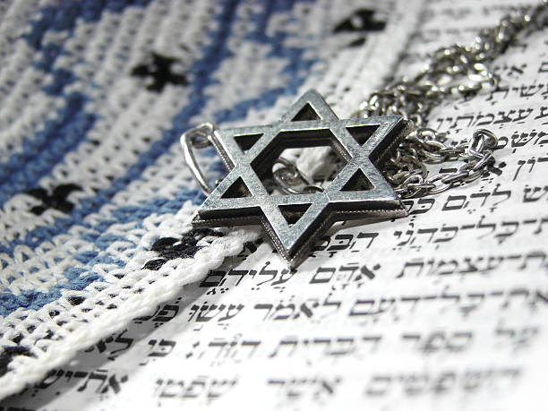 Jewish religious symbols closeup 3 Jewish religious symbols - star of David, Torah hebrew, yarmulke - closeup. judaism stock pictures, royalty-free photos & images