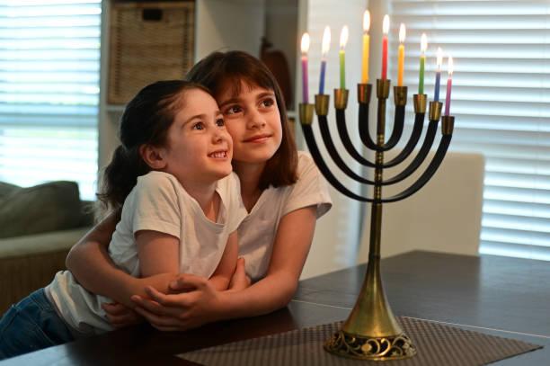 Jewish sisters looking at a beautiful menorah candelabra on  Hanukkah Jewish holiday stock photo