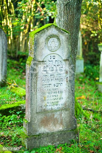 Essen, Germany - October 12, 2014: Old jewish tombstone and grave with hebrew text and yellow star. Stone is mossy. Grave on small jewish cemetery in woods in southern outskirts of Essen Kettwig, Graves are from 19th century til 1940ies.
