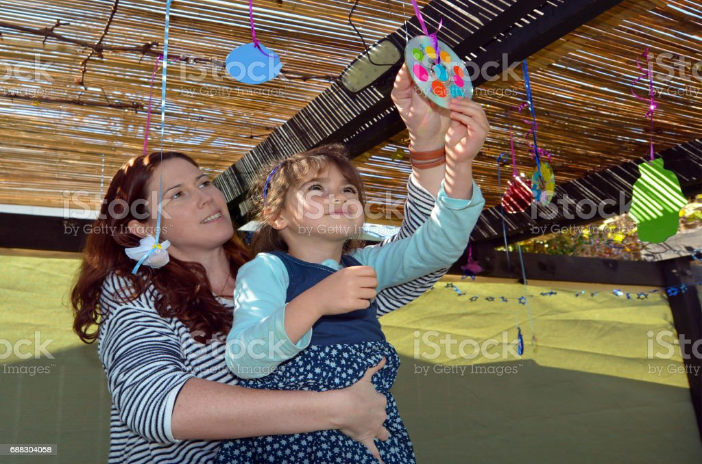 Jewish woman and child decorating their family Sukkah stock photo