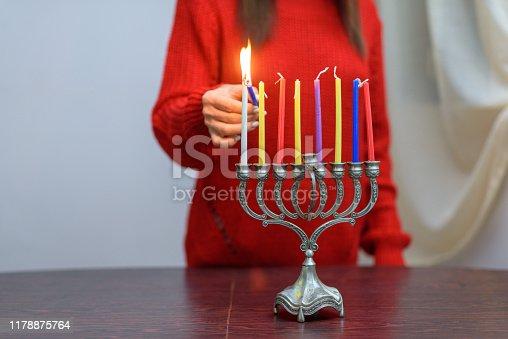 istock Jewish Woman lighting Hanukkah Candles in a menorah. 1178875764