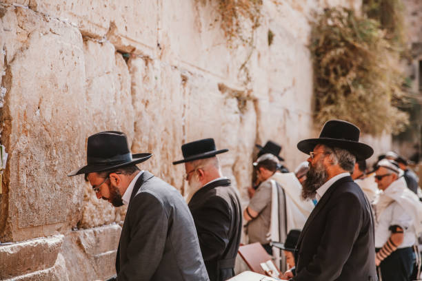 Jews Praying at Western Wall Jerusalem, Israel - November 1st, 2016: Jewsih orthodox belivers reading Torah and praying facing Western Wall, also known as Wailing Wall or Kotel in Old City in Jerusalem, Israel. It is small segment of the structure which originally composed the western retaining wall of the Second Jewish Temple atop the hill known as the Temple Mount to Jews and Christians. east jerusalem stock pictures, royalty-free photos & images