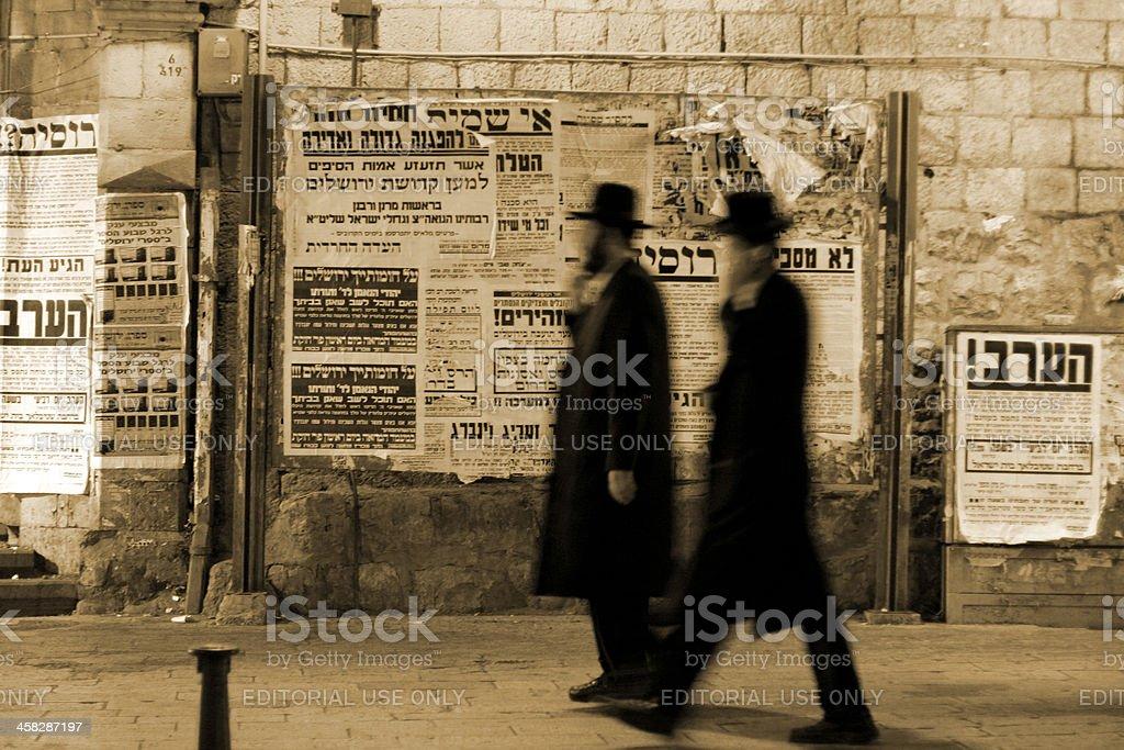 Jews walking by propaganda panels stock photo