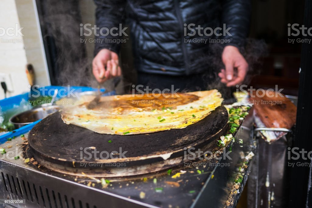 Jianbing - Asian Crepe - Scallions being spread stock photo