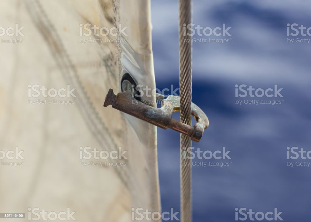 Jib hank (stags) on a forestay, heavely used. Holding a jib on a sailboat. Blurred blue background stock photo