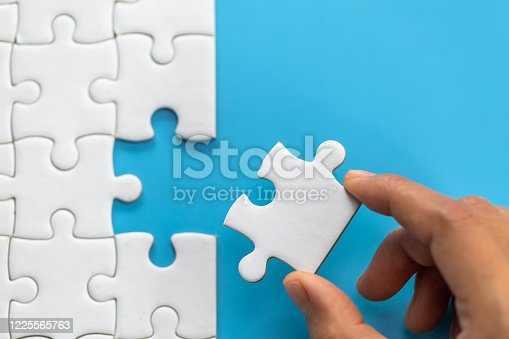 Jigsaw connection between white  jigsaw puzzles, Jigsaw puzzle in the hand of a businessman,  Business team assembling Jigsaw puzzle.