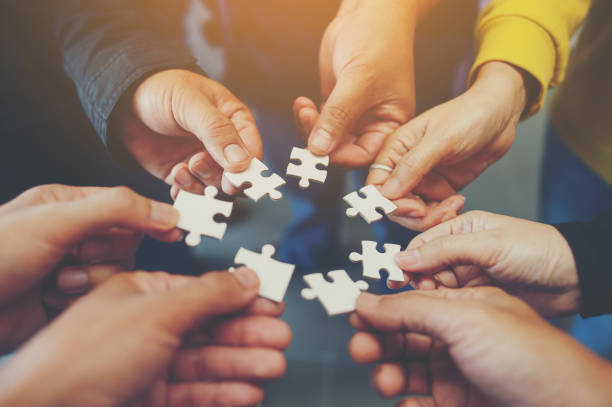 jigsaw is a harmony among the group will not be impossible. - teamwork stock photos and pictures