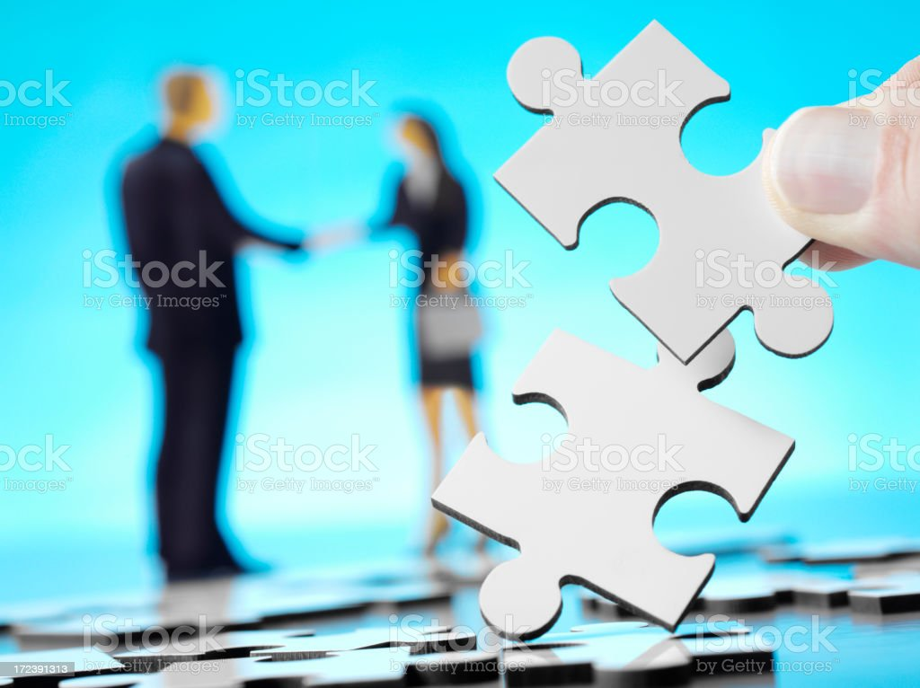 Jigsaw Pieces with a Businessman and Women Shaking Hands royalty-free stock photo