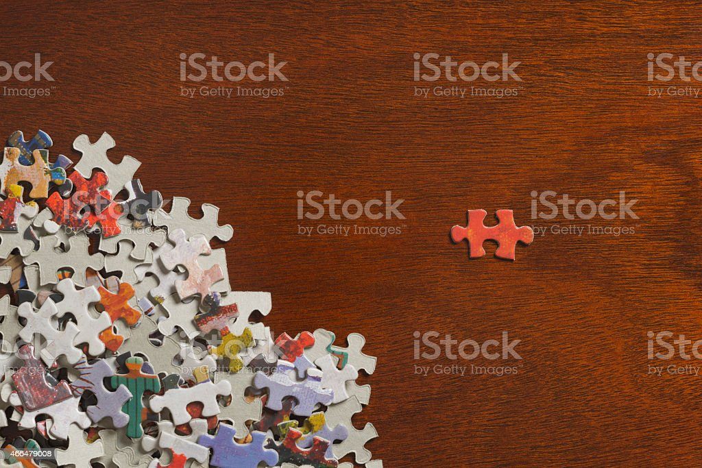 Jigsaw puzzle box with single piece separated on wooden table stock photo