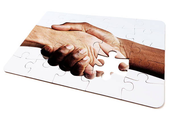 Jigsaw puzzle design of interracial handshake, with one piece missing stock photo