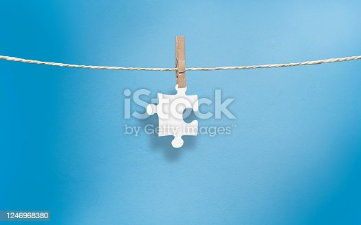 Cut out Jigsaw Puzzle icon in white cut out paper on blue background. High resolution image with copy space.