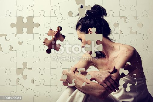 istock Jigsaw puzzle of a mature brunette woman sitting and contemplates the realities of life 1295429934