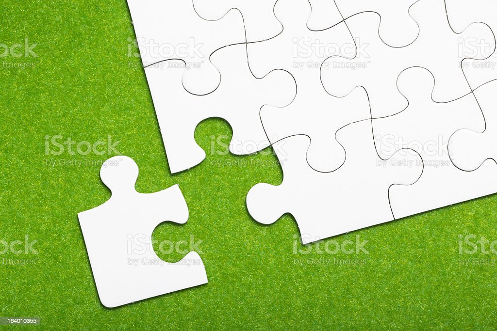 Jigsaw puzzle on green background royalty-free stock photo
