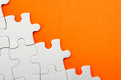 Jigsaw puzzle on orange background with copyspace
