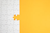High angle view of jigsaw piece and puzzle on yellow background with copy space