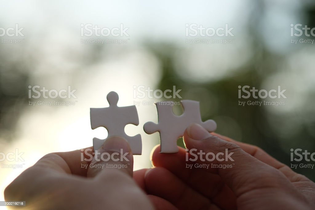 Jigsaw puzzle pieces in asian businessman against sunset or sunrise. Business concept. Completing final task. stock photo