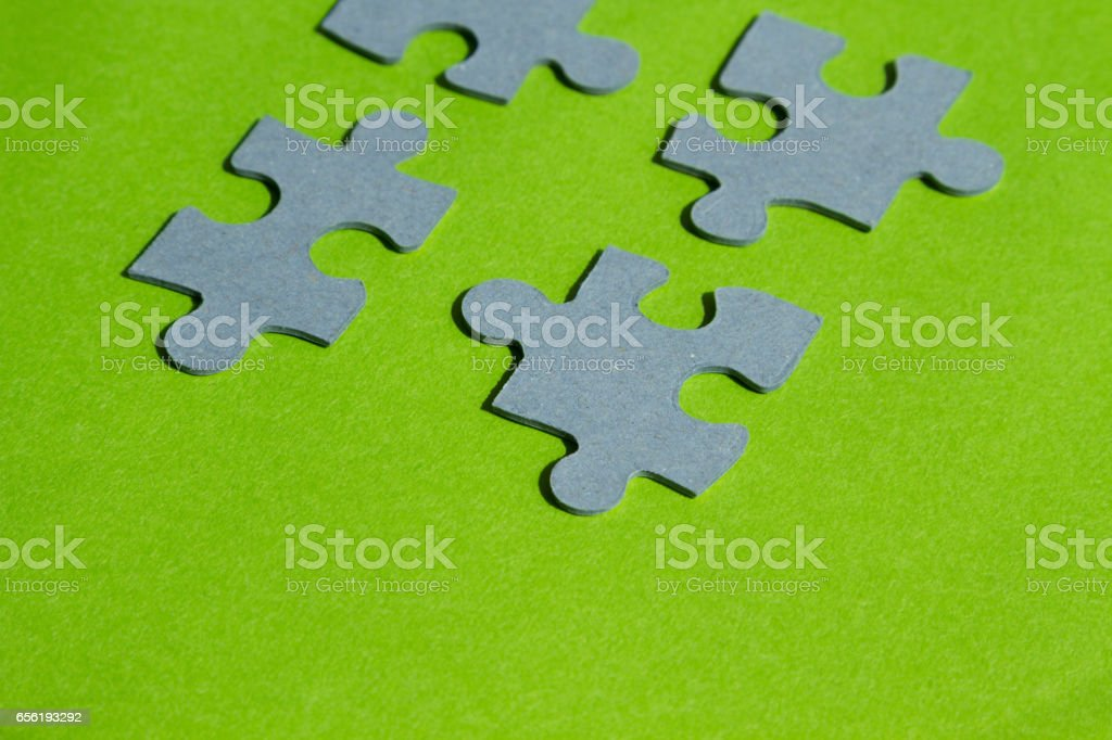 Jigsaw puzzle pieces on bright green background, horizontal view with copy space stock photo