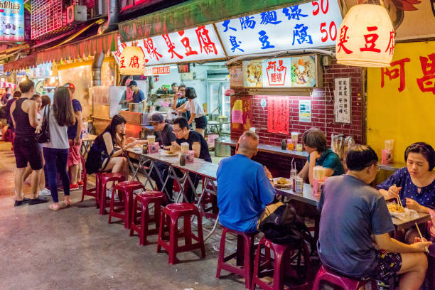 Jingmei night market street food Taipei: This is a night scene of Jingmei night market where many local Taiwanese people come at night to eat various types of Taiwanese food on July 02, 2017 in Taipei night market stock pictures, royalty-free photos & images