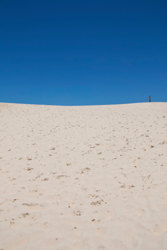 Florianopolis, Santa Catarina, Brazil - January 18, 2010: Panoramic view of a Brazilian dunes called Joaquina located in Florianopolis city in Santa Catarina state with many tourists enjoying and renting the sandboards to slide on the dunes in a sunny day with a clear sky on it.