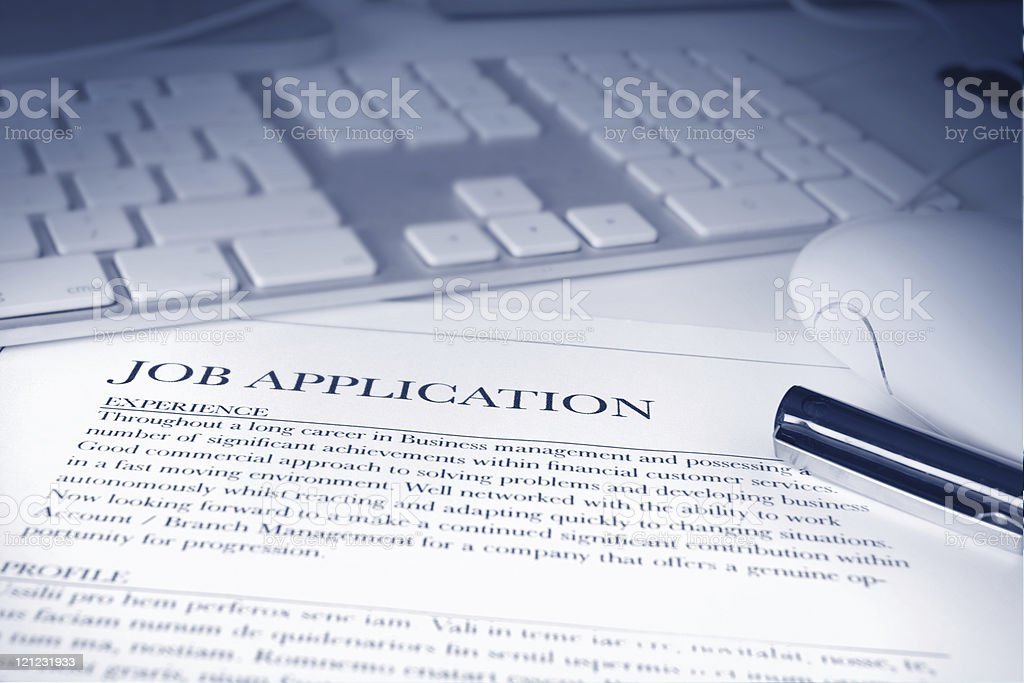 Job application form next to a pen and a laptop stock photo