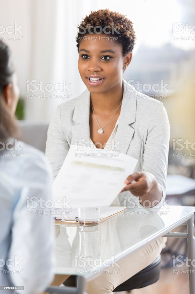 Job candidate hands resume to interviewer stock photo