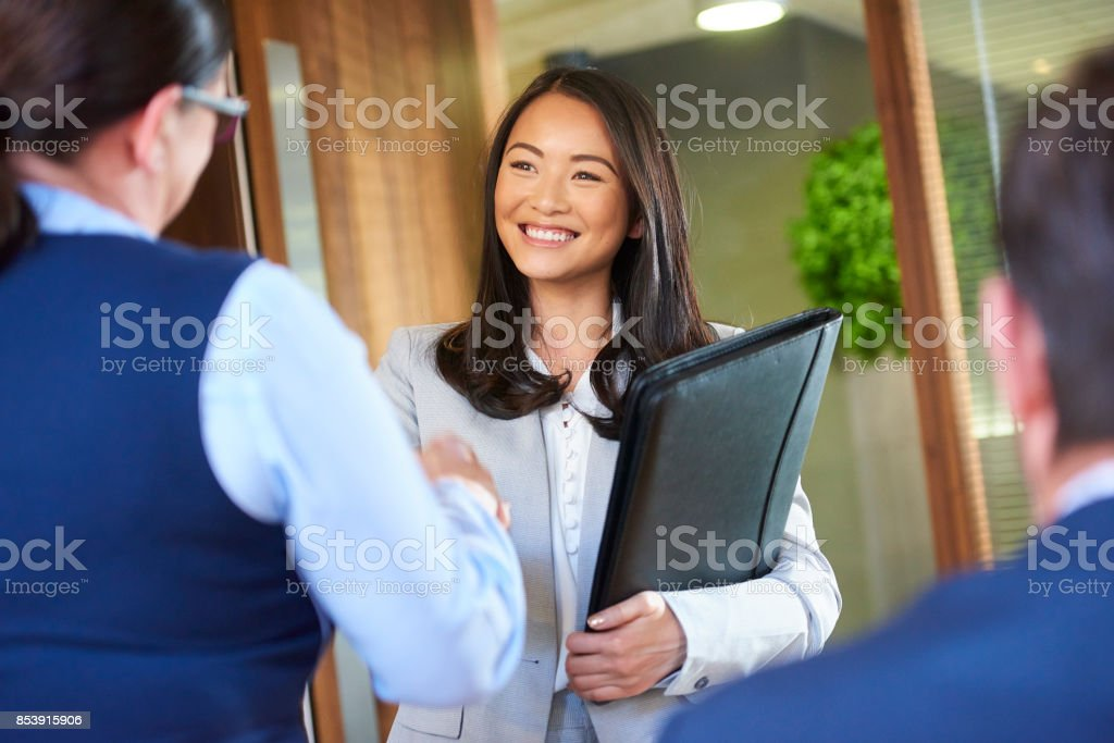 job candidate smiling as she enters the interview stock photo