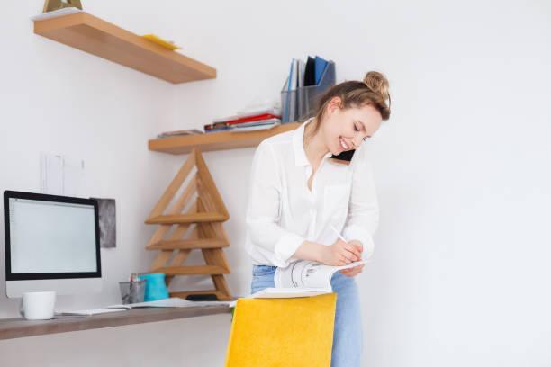 job, karriere, beruf und erfolg konzept. erfolgreiche weibliche projektleiter hat telefongespräch mit client an einem harten arbeitstag im kreativbüro - telefonschrank stock-fotos und bilder