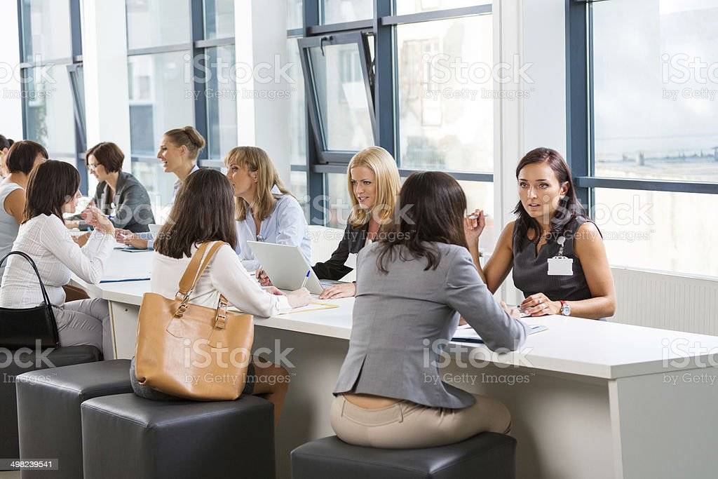 Job fair Group of women attending a job fair, working together and discussing. 30-39 Years Stock Photo