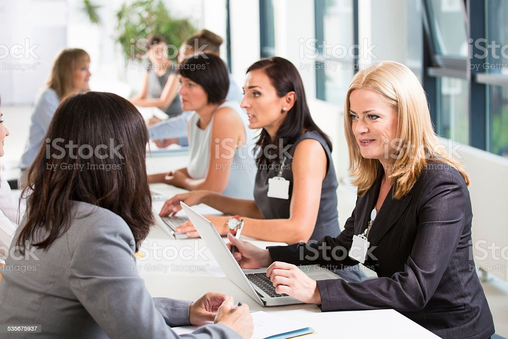 Job fair Group of women attending a job fair, working together and discussing in an office. 2015 Stock Photo