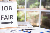 Job fair table with employment applications, resumes.