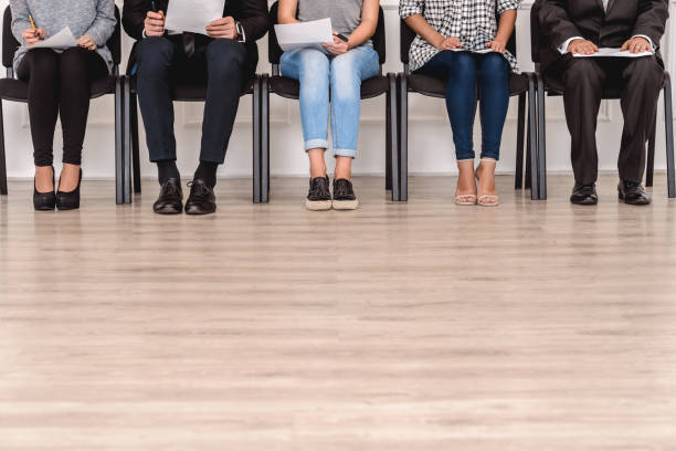Job Interview. Candidates sitting waiting with resumes floor and legs close-up stock photo