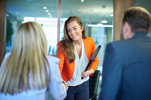 a young graduate walks into an interview room full of confidence and positivity energy . She is holding her cv and smiling at the interview panel before her. She is wearing blue trousers with an orange suit jacket , as she opens the door and strides in and shakes hands with a woman on the panel . in the foreground we can see the back of two of the panel , a man and a woman.