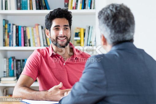 Job interview of brazilian male apprentice with businessman at office