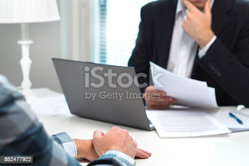 963814372istockphoto Job interview or meeting with bank worker in office. Business man considering. Discussion about loan, mortgage or insurance. Human resources conversation. Hiring or getting fired. Thoughtful man. 852477922