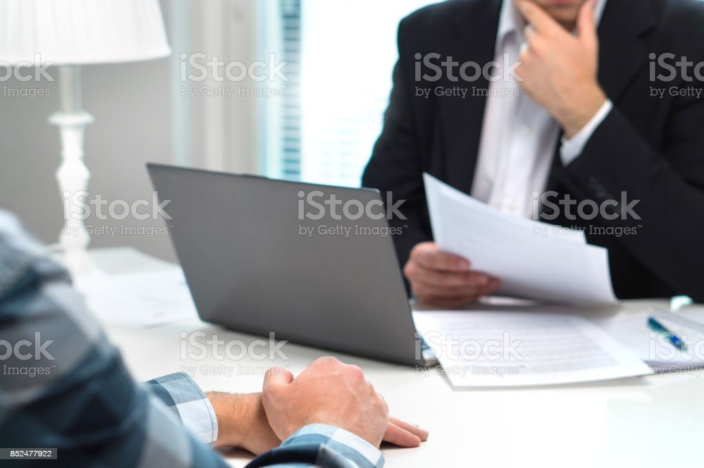 Job interview or meeting with bank worker in office. Business man considering. Discussion about loan, mortgage or insurance. Human resources conversation. Hiring or getting fired. Thoughtful man. stock photo