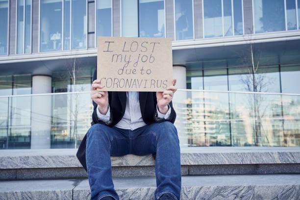 "job loss due to covid-19 virus pandemic concept. unrecognizable man holds sign ""i lost my job"" - unemployment стоковые фото и изображения"